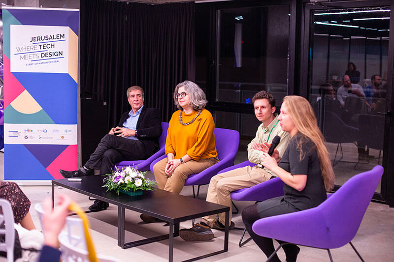 Two men and two women sitting in purple chairs speaking on a panel